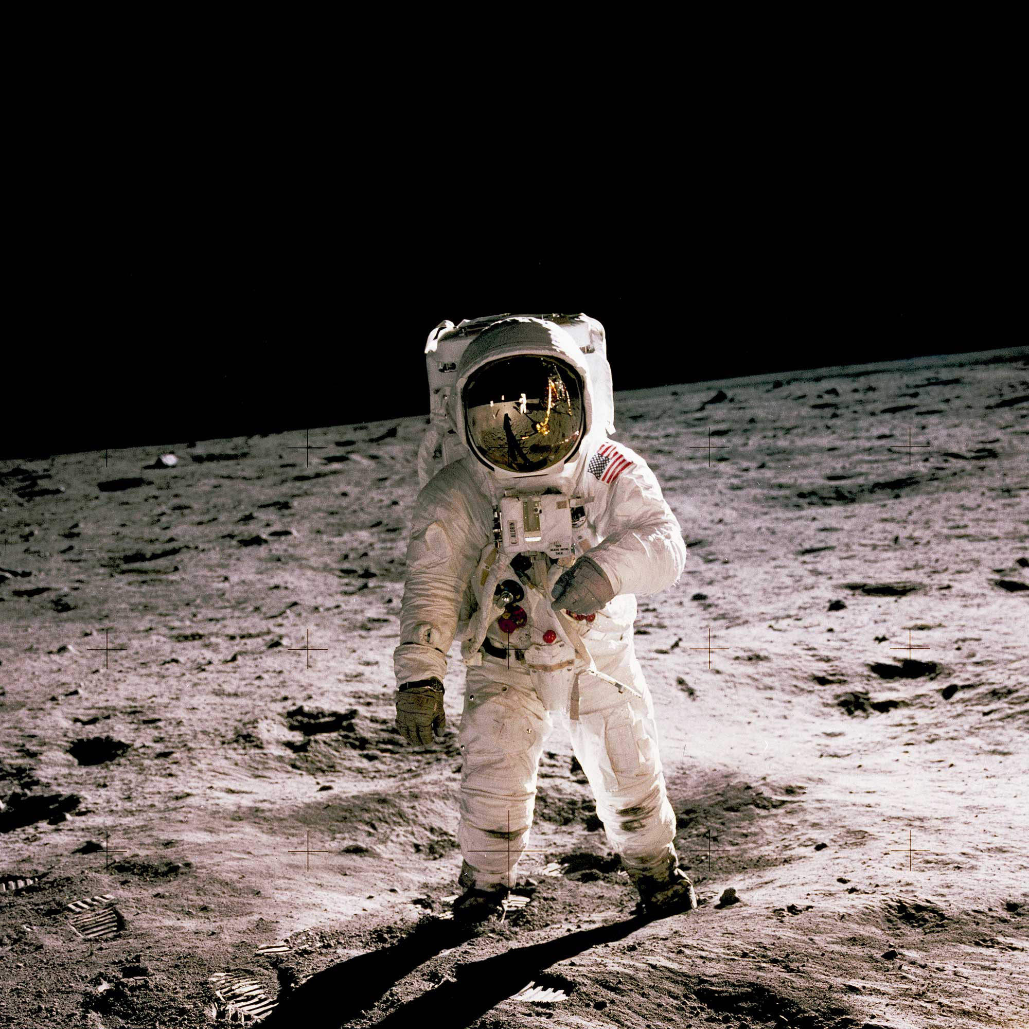 Buzz Aldrin walking on the lunar surface with Neil Armstrong reflected in Aldrin's visor